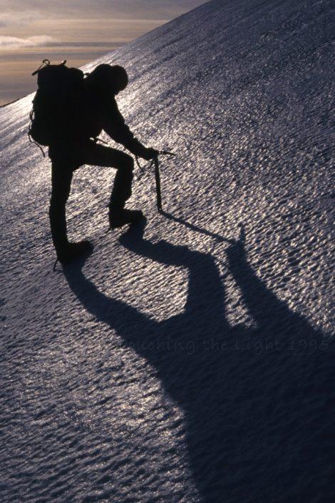 Silhouette climber on steep ice, Ben Alder, Scottish Highlands